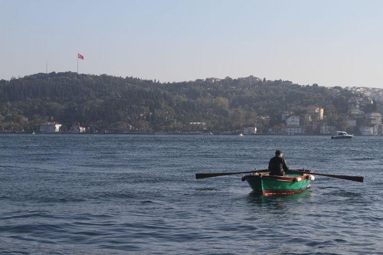 Rear view of man oaring boat in sea against sky