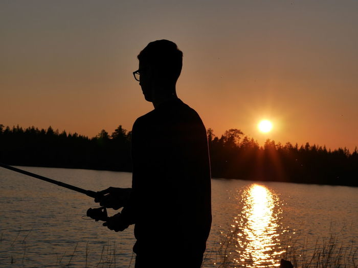 Fishing near the arctic circle. Back Lit Beauty In Nature In Front Of Lake Leisure Activity Lens Flare Men Mountain Nature Orange Color Outdoors Scenics Silhouette Sky Standing Sun Sunbeam Sunlight Sunset Tranquil Scene Tranquility Tree Vacations Water