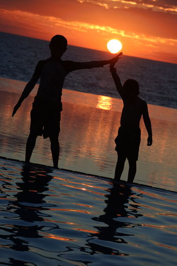 Silhouette boys standing by infinity pool against sea during sunset