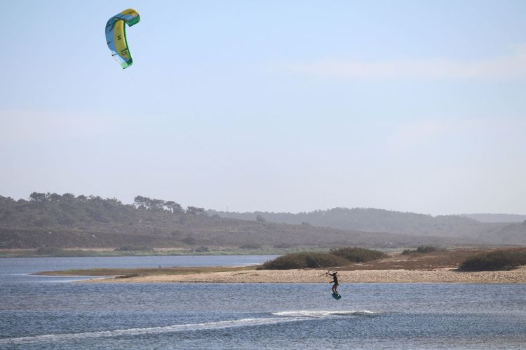 Person kiteboarding on sea against sky