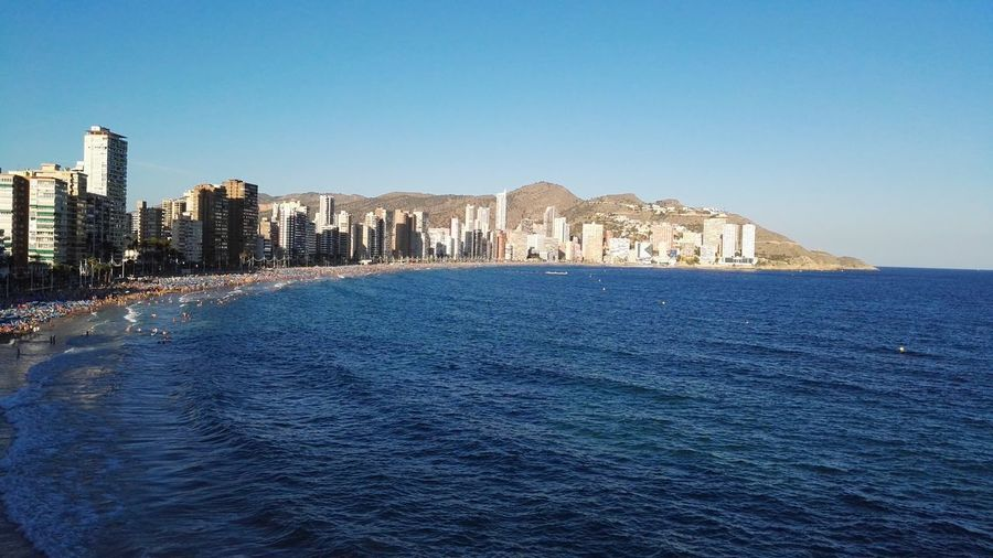 View Of Calm Sea In Front Of City Against Clear Blue Sky