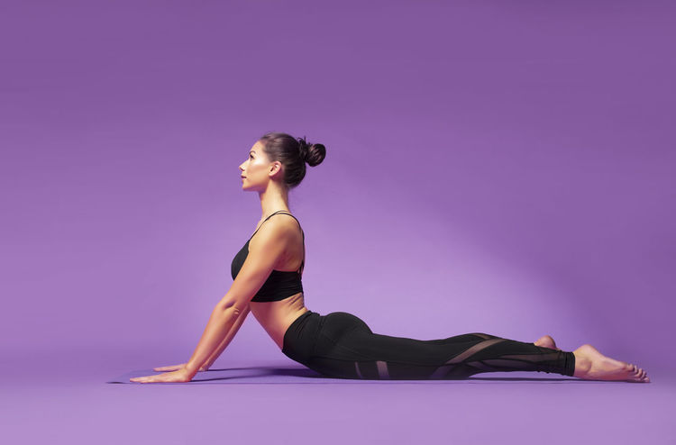 Long haired beautiful pilates or yoga athlete does a graceful pose while wearing a tight sports outfit against a bright purple background in a studio Body & Fitness Dance Exercising Silhouettes Stretching Legs Workout Flow Yoga Pose Abdominal Muscles Art Background Exercise Ball Fitness Outfit Long Hair Pilates Pilateslovers Pink Color Pose Pretty Girl Rubber Band Sports Clothing Studio Shot