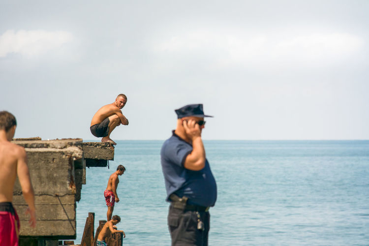 A swim short wearing male looks at the camera whilst preparing himself to dive from an old concrete pier in to the Black Sea, Batumi, Georgia. Day Group Of People Hat Holiday Horizon Horizon Over Water Land Leisure Activity Men Nature Outdoors People Real People Sea Sky Standing Three Quarter Length Trip Vacations Water
