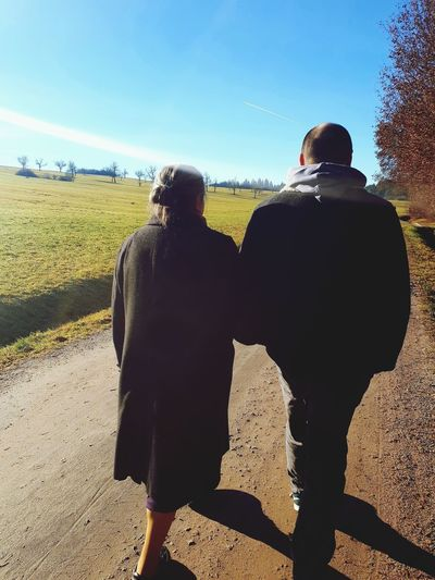 Rear view of couple on land against sky