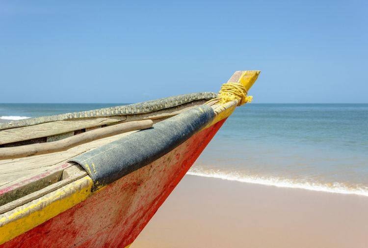 Close-up of boat on beach against clear sky