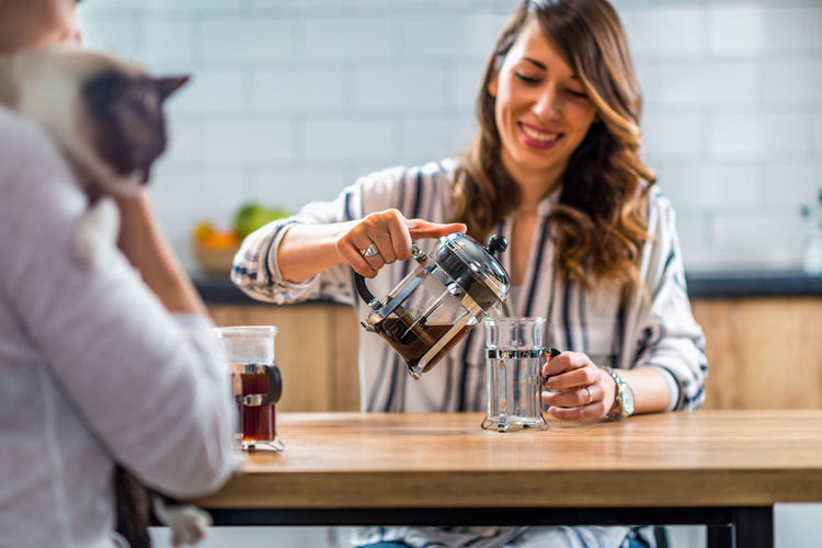 Girlfriends Having Coffee Together Coffee French Press Females Women Cafe Home Drink Young Girl Cup Hot Glass Two People Enjoy People Caucasian Happy Lifestyle Concept Caffeine Indoors  Holding Beautiful Adult Casual Enjoyment Break Table Aroma Woman Close Up Drinking Happiness Smiling Cat Morning Young Women Indoors  Emotion