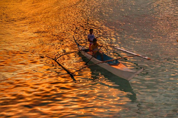 Man in boat sailing on water