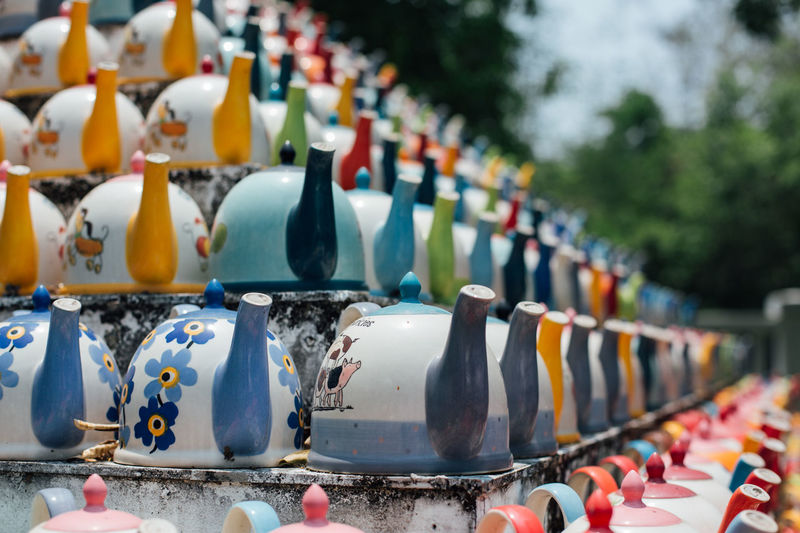 Close-Up Of Multi Colored Teapots In Row At Market