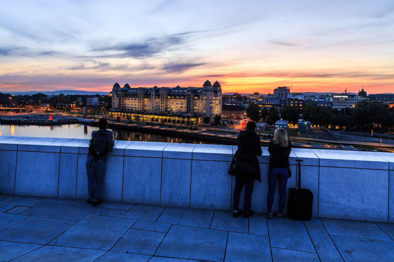 People on illuminated city by river against sky during sunset