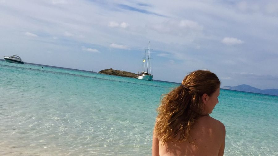 Rear View Of Topless Woman By Sea Against Cloudy Sky At Formentera