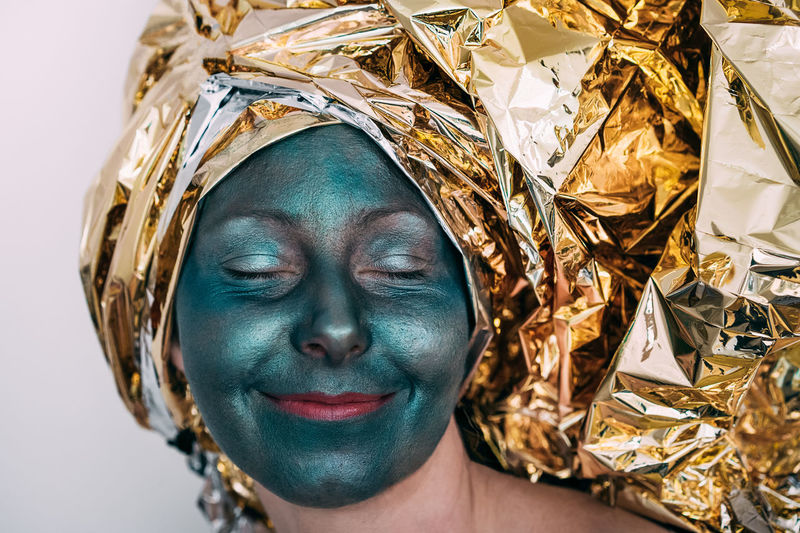 Close-up of woman with green facial mask wearing golden foil