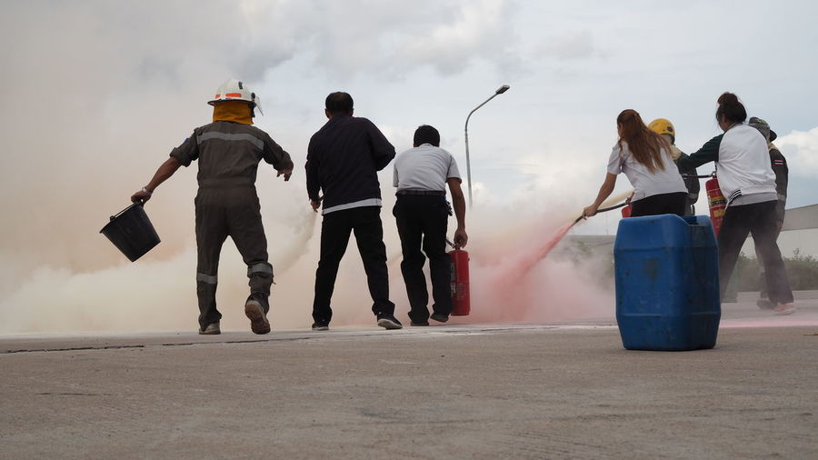 Rear view of people spraying water on fire against sky