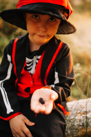 Portrait of boy wearing costume during halloween holding blackberries at forest