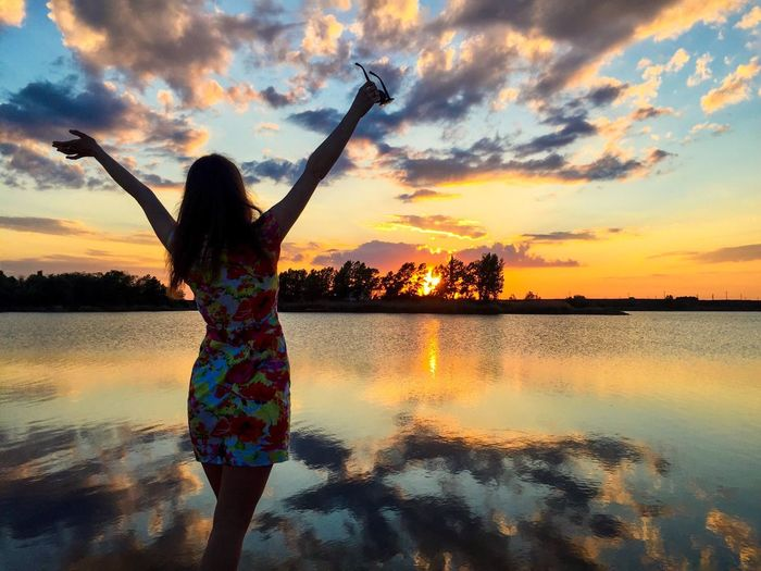 Woman with hands up in the air watching the sunset near the lake Sunset Reflection Sky Water Orange Color Silhouette One Person Cloud - Sky Nature Beauty In Nature Outdoors Standing Scenics Leisure Activity Tranquil Scene Tranquility Lifestyles Real People Full Length Woman Dress Summer Lake Clouds