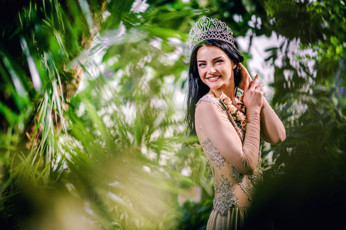 Elegant smiling lady with tiara on a head posing in a forest Crown Diadema Elégance Evening Gown Princess Summertime Sunlight Tiara Well-dressed Woman Beautiful Woman Beauty Botanical Garden Brunette Diadem Evening Dress Forest Garden Looking At Camera Lush Foliage Nature One Person Outdoors Smiling Young Adult
