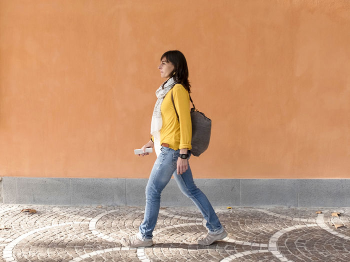 Side view of young woman standing against wall