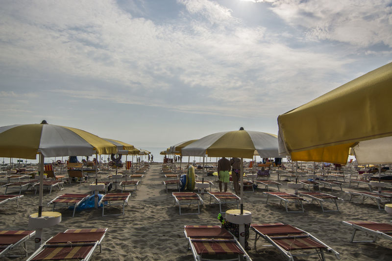 Chairs and parasols at beach against sky