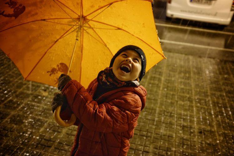 Full length of happy man holding umbrella in rain