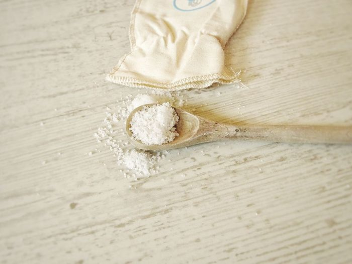 High angle view of sea salt on a wooden spoon