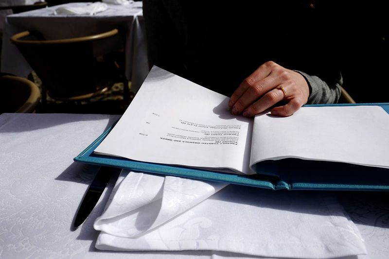Woman hand on document at table in restaurant