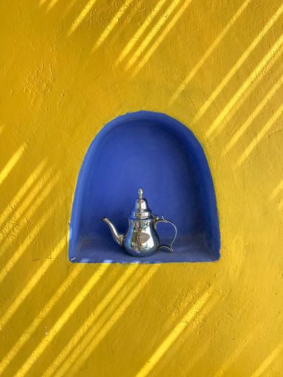 Close-up of tea kettle in niche on yellow wall