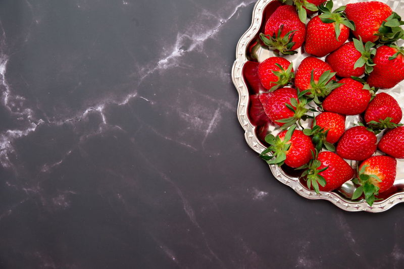 High angle view of strawberries on table against black background