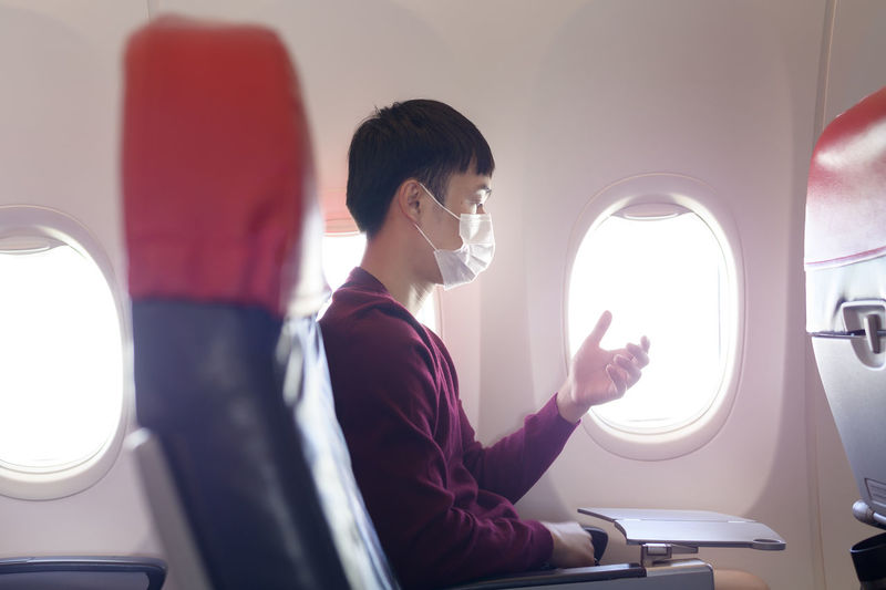 Side view of man looking through airplane window