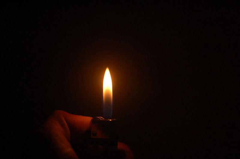 Cropped hand holding lighter in darkroom