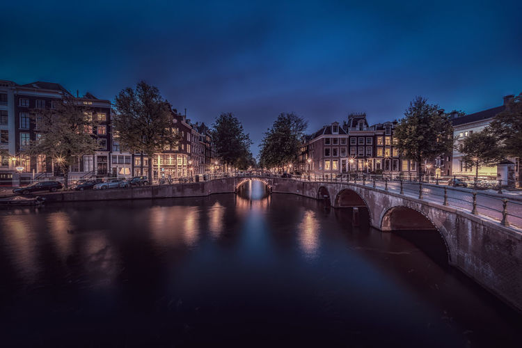 Bridge over river by illuminated buildings against sky in city