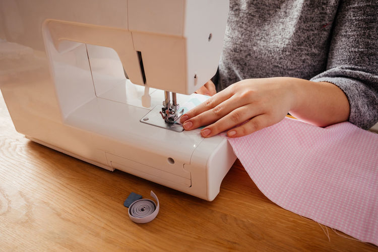 Midsection of woman using sewing machine