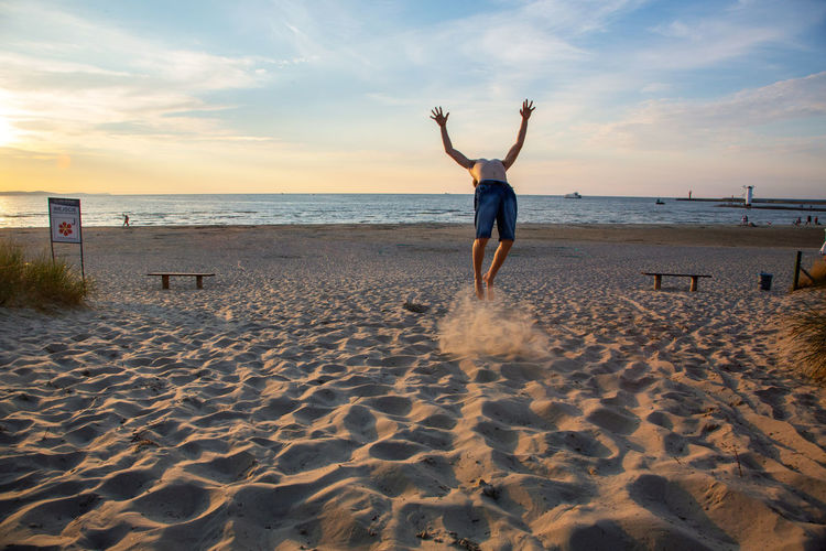 Baltic Sea Jump Arms Raised Beach Beauty In Nature Cloud - Sky Full Length Holiday Horizon Horizon Over Water Human Arm Land Leisure Activity Lifestyles One Person Real People Sand Scenics - Nature Sea Sky Trip Vacations Water