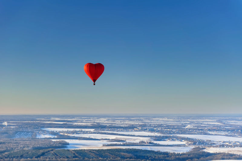 Red air balloon in the shape of heart against blue sky in a sunny day fly high above the trees