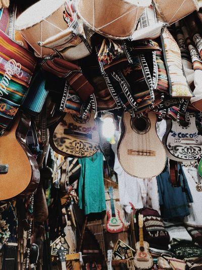 Low angle view of guitars and clothes for sale at market
