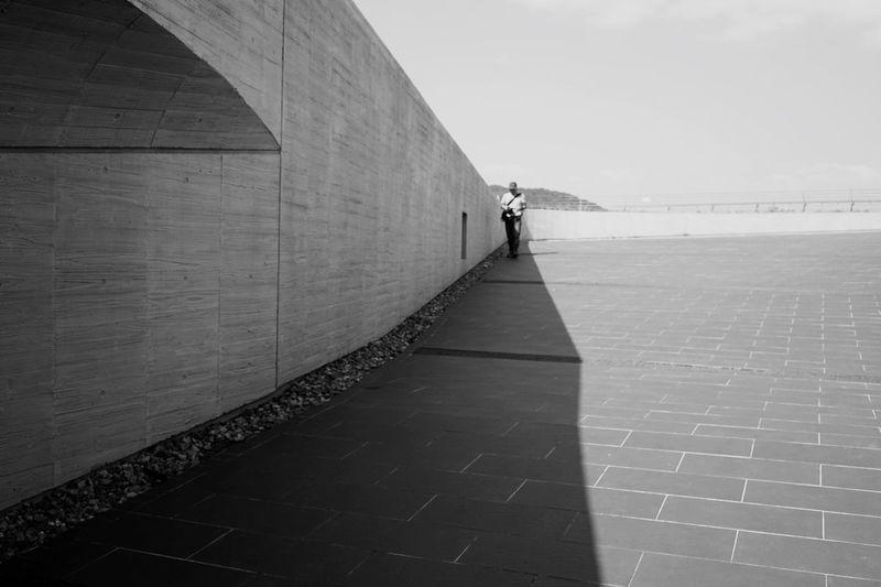 Man walking on footpath against sky