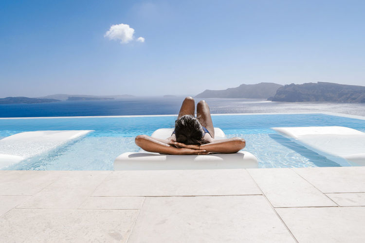 Woman relaxing in swimming pool by sea against sky