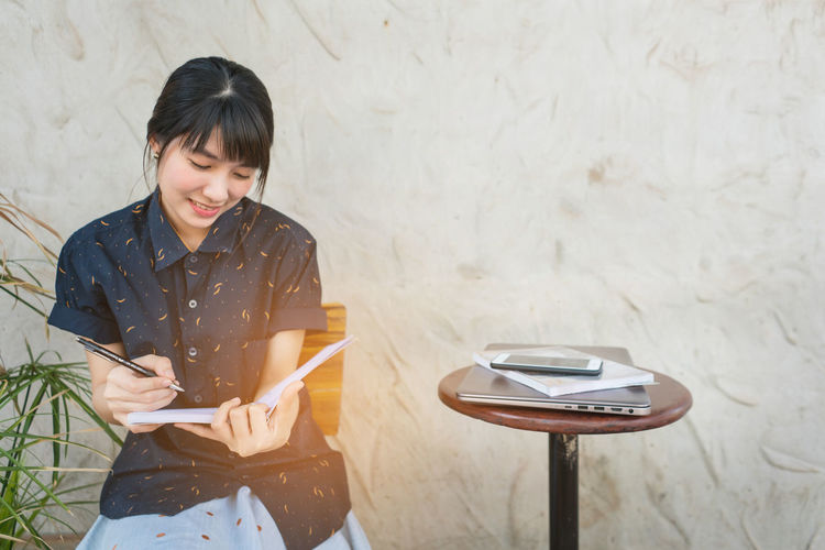 Woman Writing In Book While Sitting Against Wall