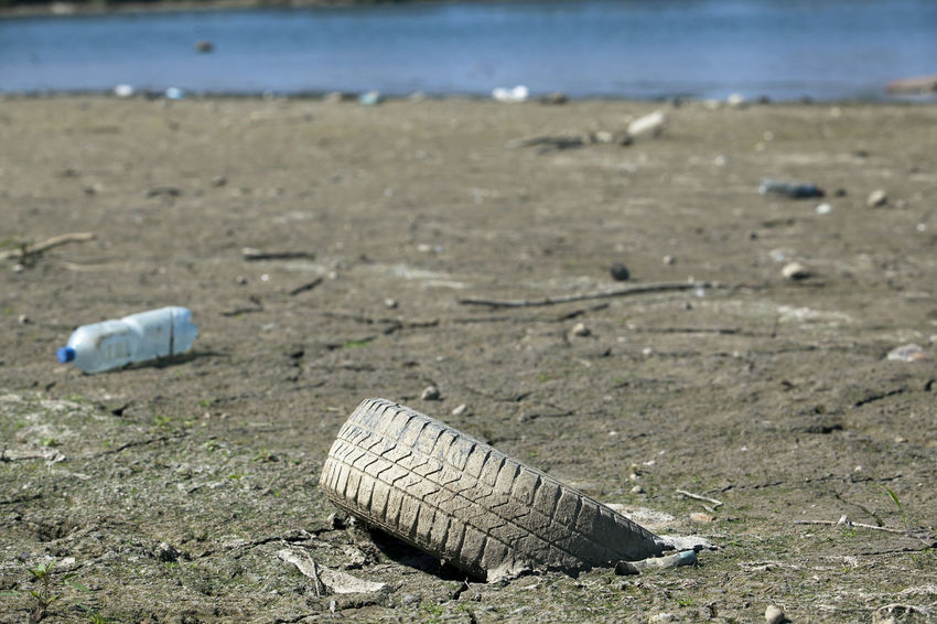 Od used car tire in the nature Environmental Pollution Riverside Abandoned Beach Car Car Tire Car Tyre Day Environment Nature No People Old Outdoors Pollution River Rubber Sand Tire Tyre Used Waste Water Waterside