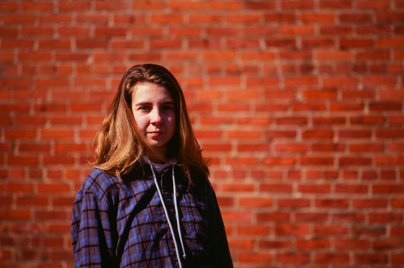 Young woman in front of old brick wall