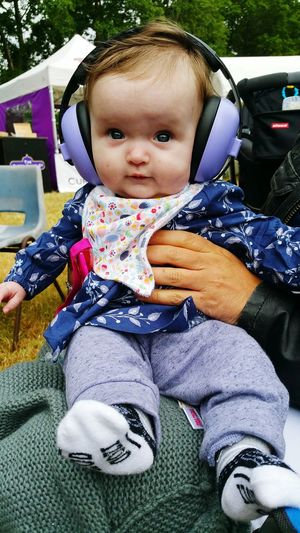 Baby Portrait Cute Smiling Looking At Camera Leisure Activity Outdoors Babies Only Real People Happiness Sitting Day Ear Defenders 1st Festival Music Festival Purple Crowd Summer Babyhood Festival Festival Season Blues Caring Young And Beautiful Lifestyles