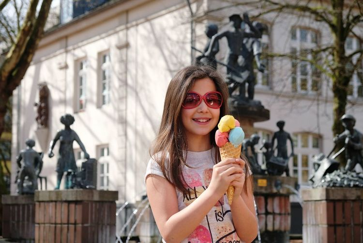 Portrait Of Happy Girl Having Ice Cream Cone In City