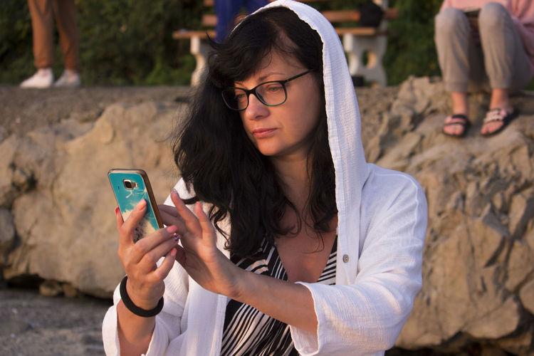 Portrait of beautiful woman with hood at sunrise light, using smart phone