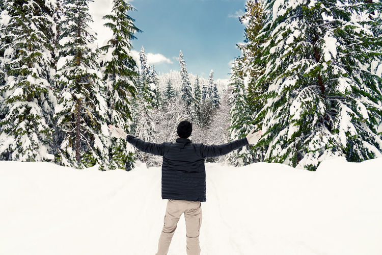 Rear View Of Mature Man With Arms Outstretched Standing In Forest During Winter