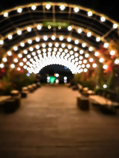 Beaty of lights City Illuminated Defocused Carousel Amusement Park Ride Tunnel The Way Forward Empty Road Road Marking vanishing point Light At The End Of The Tunnel
