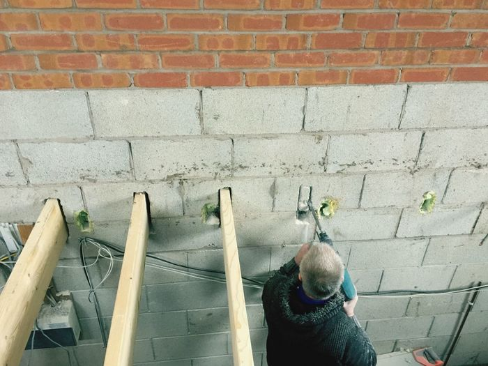 Rear view of man walking against brick wall