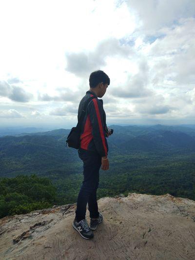 Full length of boy standing on mountain against sky