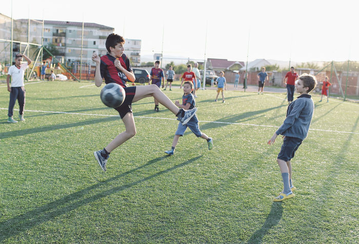 Ball City Life Competition Competitive Sport Field Football Fun Grass Grassy Green Color Jumping Large Group Of People Lawn Leisure Activity Lifestyles Mixed Age Range Outdoors Playing Running Soccer Sport Sunset People Together People And Places Snap A Stranger