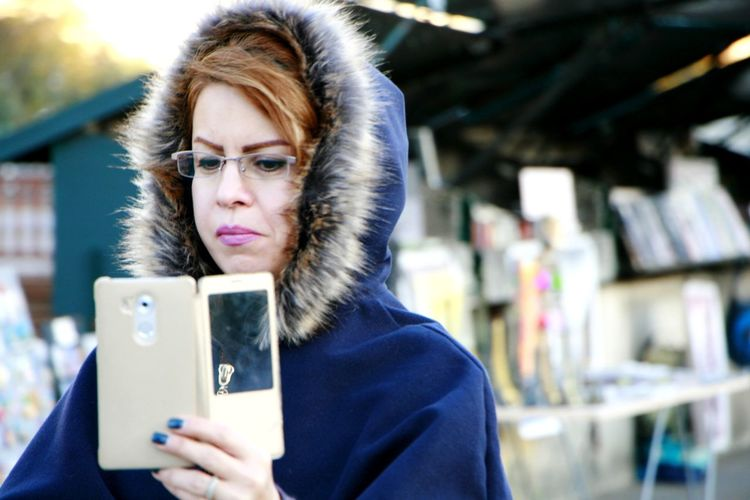 Woman wearing warm clothing using smart phone in city