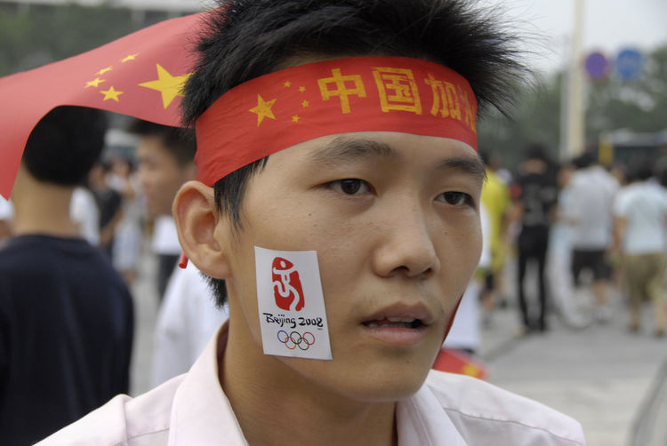 Beijing Olympics China Chinese Patriotism Close-up Communication Day Focus On Foreground Front View Headshot Incidental People Leisure Activity Lifestyles Looking At Camera One Person Outdoors Patriotism Portrait Real People Text Young Adult