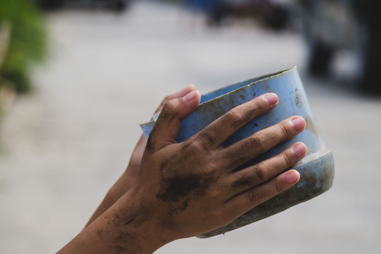 Close-up of hand holding container while begging