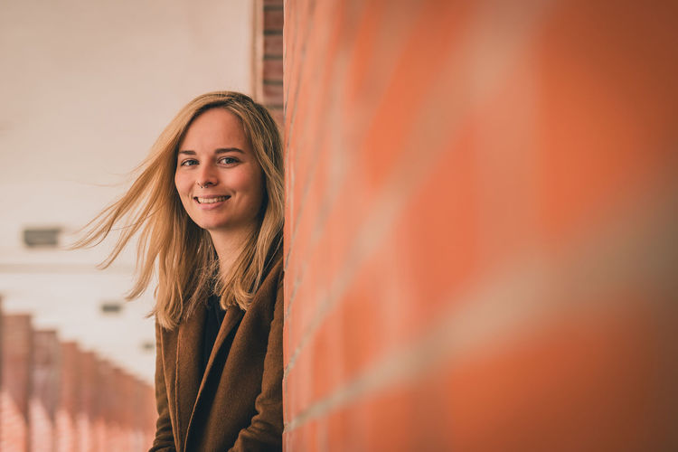 Portrait of smiling beautiful woman with blond hair standing by architectural column